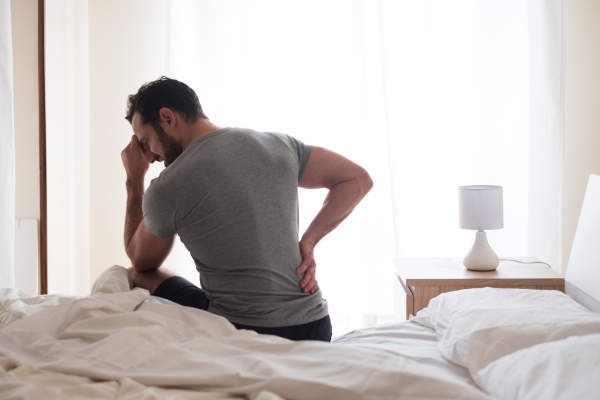man experiencing back pain in the morning