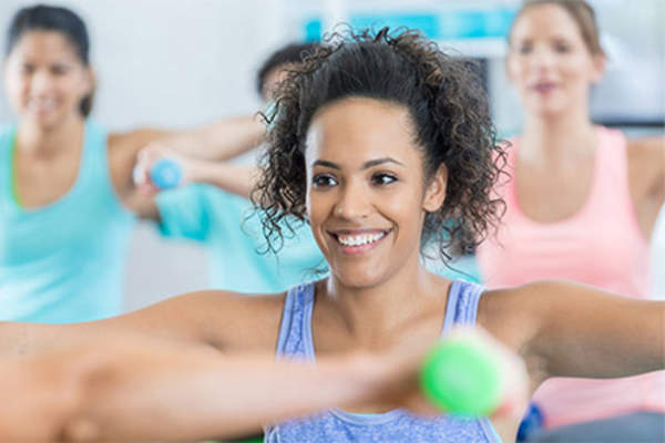 Smiling woman in group exercise class with weights.