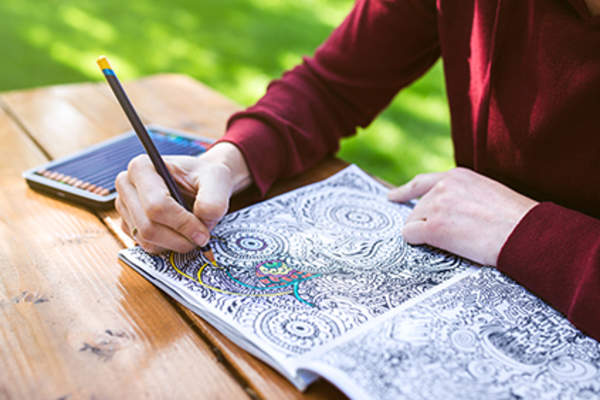 Coloring in an adult coloring book.