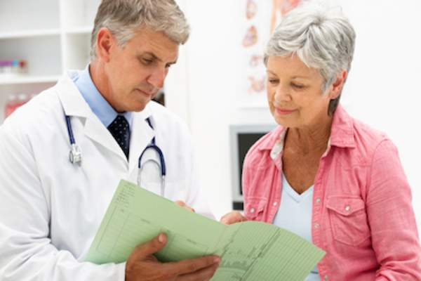 Older woman reviewing medical file with her doctor.