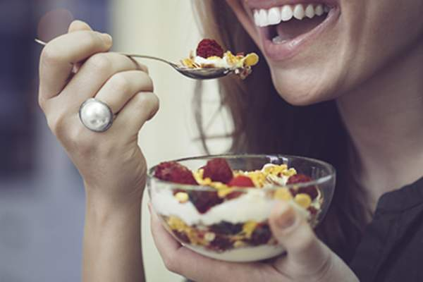Woman smiling while eating breakfast.