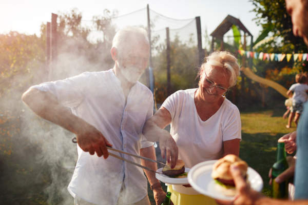 two seniors barbecuing in backyard