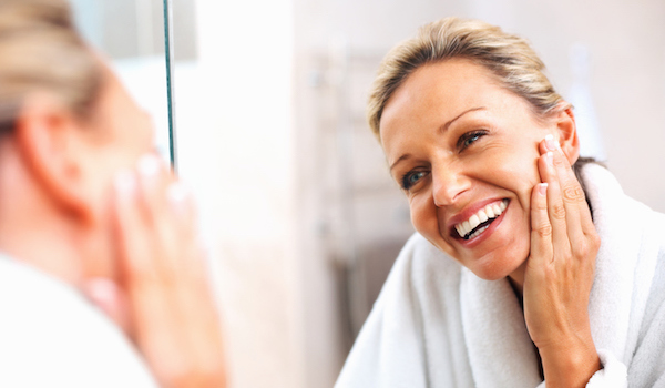 Happy older woman examining skin in mirror.