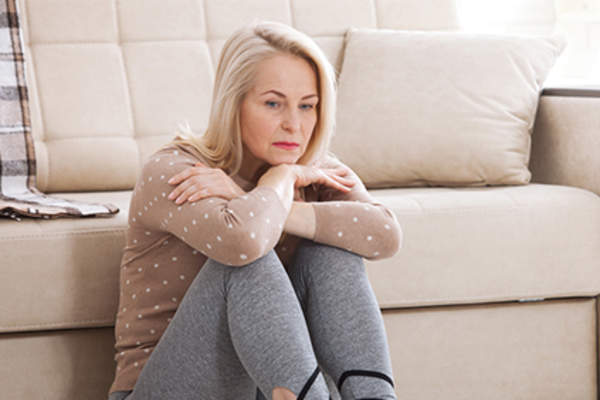 Woman leaning against the couch in a bad mood.