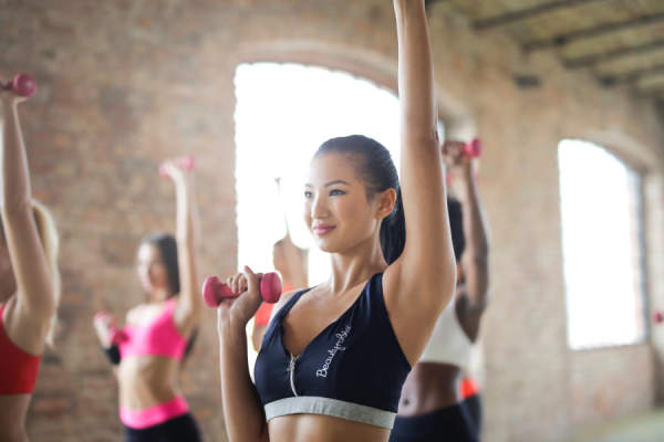 woman lifting dumbbells in workout class