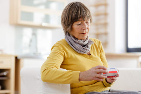 woman looking at package for medication
