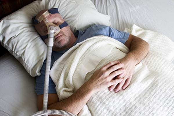 Man sleeping in bed using a CPAP.