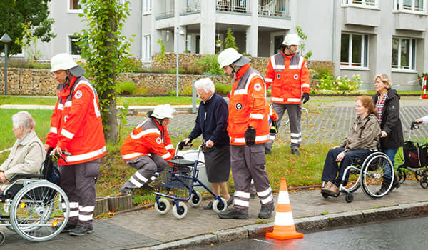 Red Cross rescue workers help senior residents.