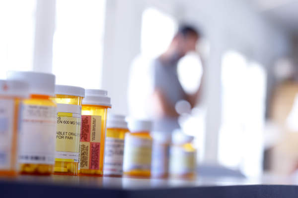 Prescription bottles lined up, out-of-focus man in the background
