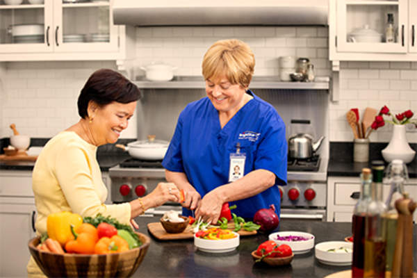 In-home caregiver cooking with woman in kitchen.
