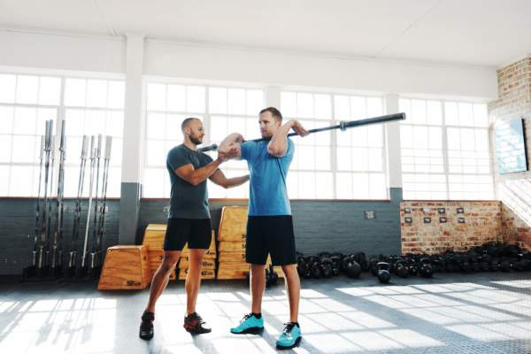 fitness instructor guiding his client