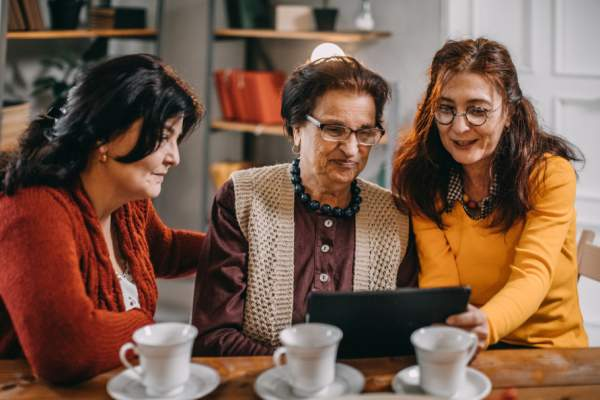 three senior women, family, looking at tablet