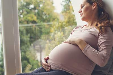Pregnant woman holding her belly and looking through a window.