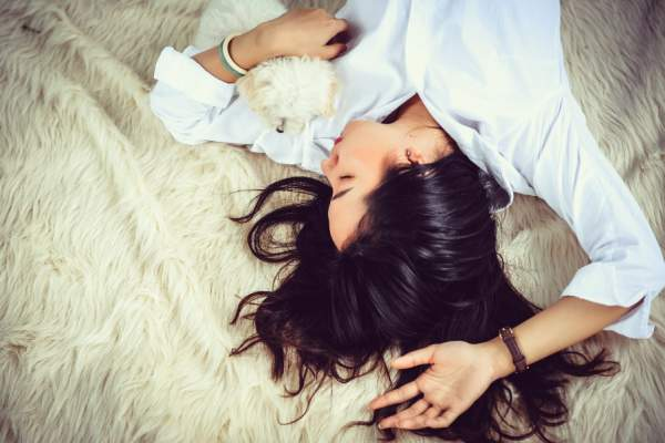 woman and puppy sleeping on bed