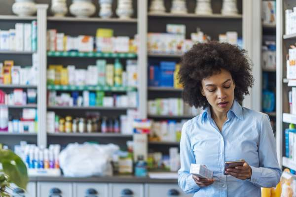 woman looking at phone will holding medicine in pharmacy