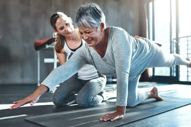 Younger woman helping senior woman at the gym