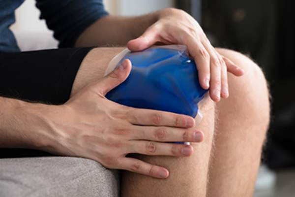 Person applying an ice pack to their knee.