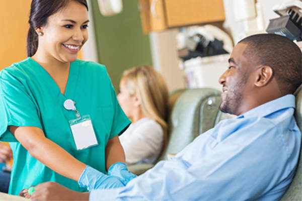 Nurse talking to smiling man in a clinical trial.