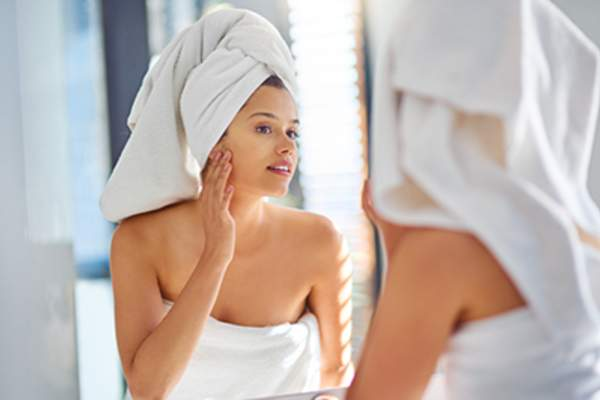 Woman in the bathroom wearing a towel on her body and head.
