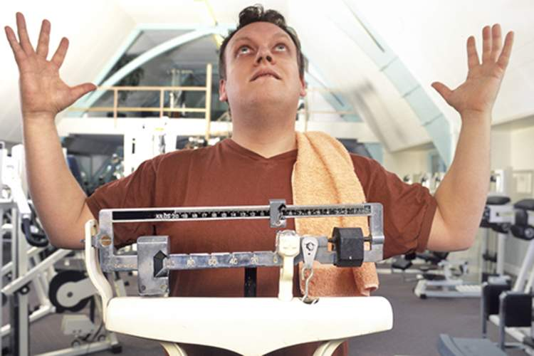 Frustrated man on scale at gym cannot lose weight.