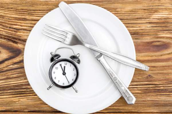 Fasting concept, plate with clock and silverware.