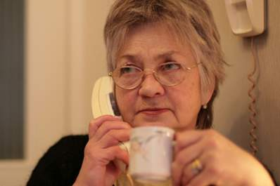 Woman takes hearing test on landline phone.