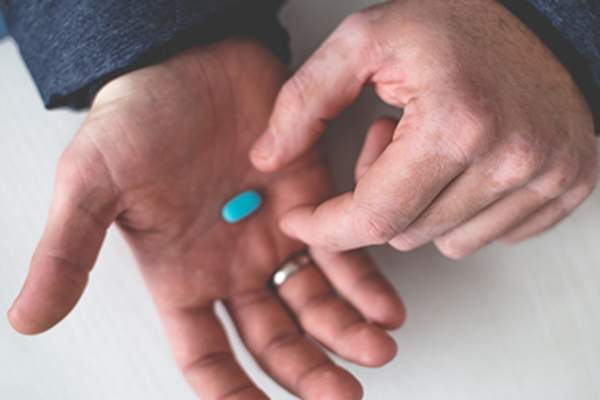 Man taking a blue pill from his hand.
