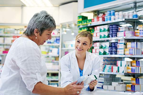 Adult woman talking to smiling pharmacist.