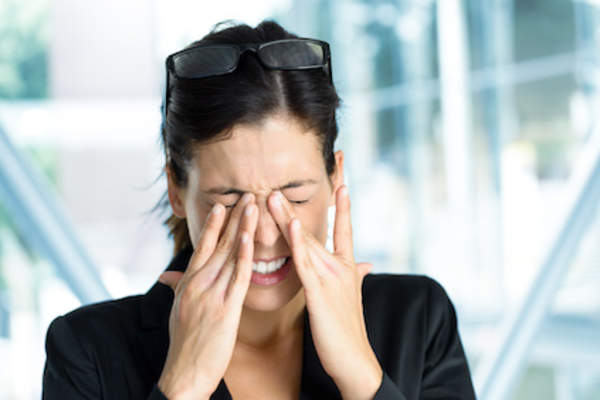 Woman rubbing sore eyes.