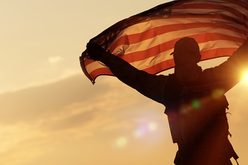 Silhouette of soldier in sunset holding American flag.