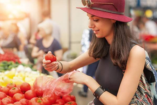 Woman looking at tomatoes at an outdoor market.