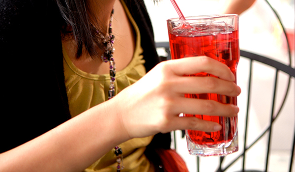 Young woman drinking glass of cranberry juice.