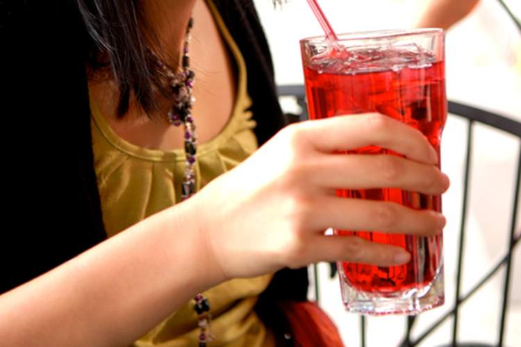 Young woman drinking a glass of cranberry juice.