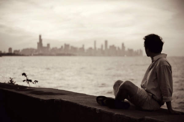 man looking out towards the skyline, moody
