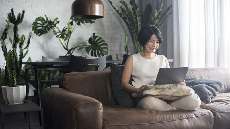 Woman on a couch using a laptop.