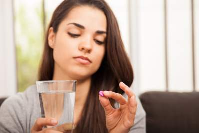 Young woman taking pill.