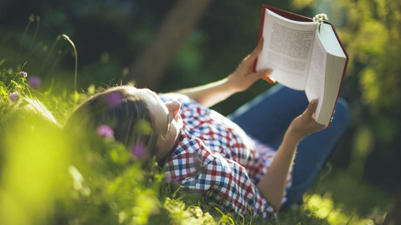 Woman reading a book while lying in the grass.