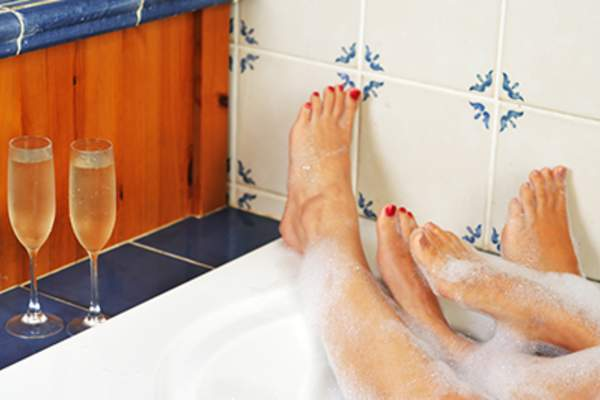 Feet of couple relaxing in the bath with champagne.