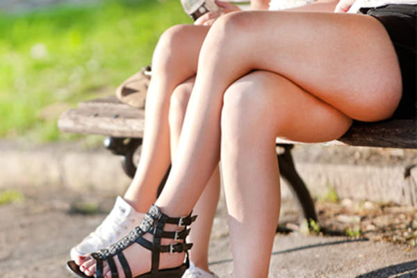 Women sitting on park bench in shorts with legs crossed.