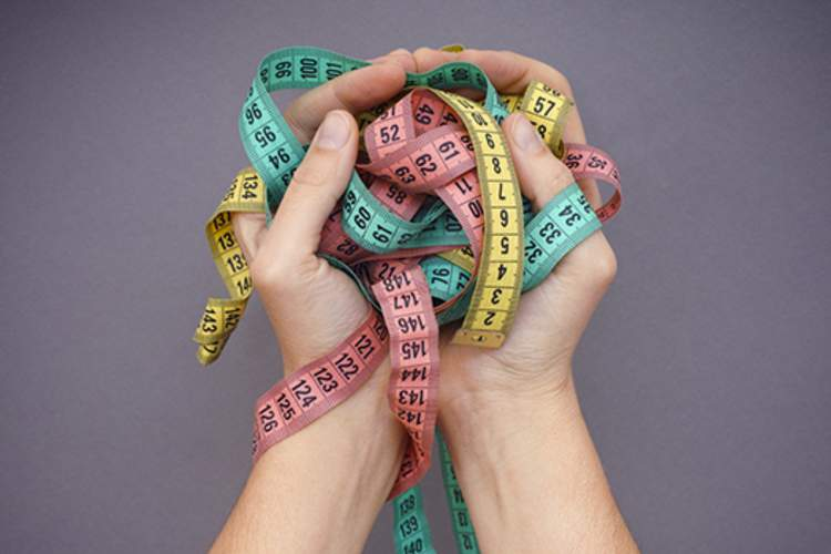 Woman holding different colored tape measures to show significant weight loss.