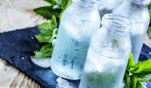 Ice cold mineral water in glass bottles image.