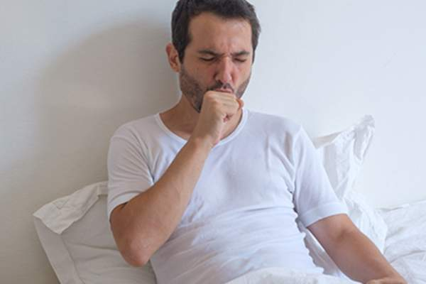 Man lying on bed and coughing.