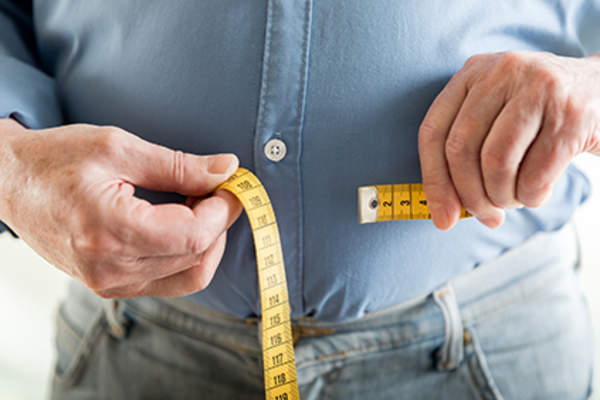 Overweight man measuring his waistline.