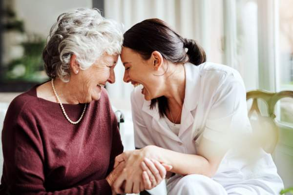 young woman laughing with senior woman
