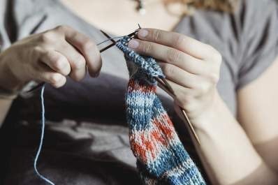 Woman trying to finish a knitting project.