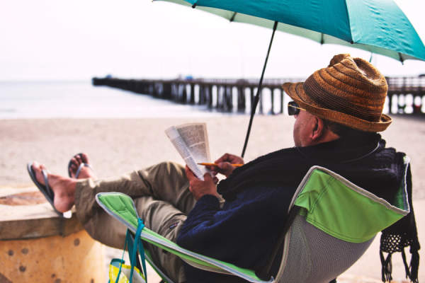 senior man reading on beach wearing sun-protecting clothes