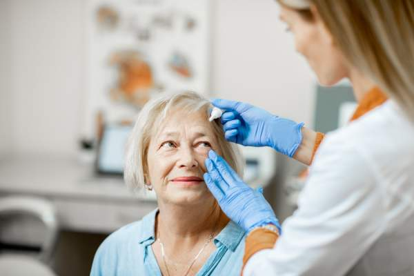 Doctor dripping eye drops on eyes of a senior patient