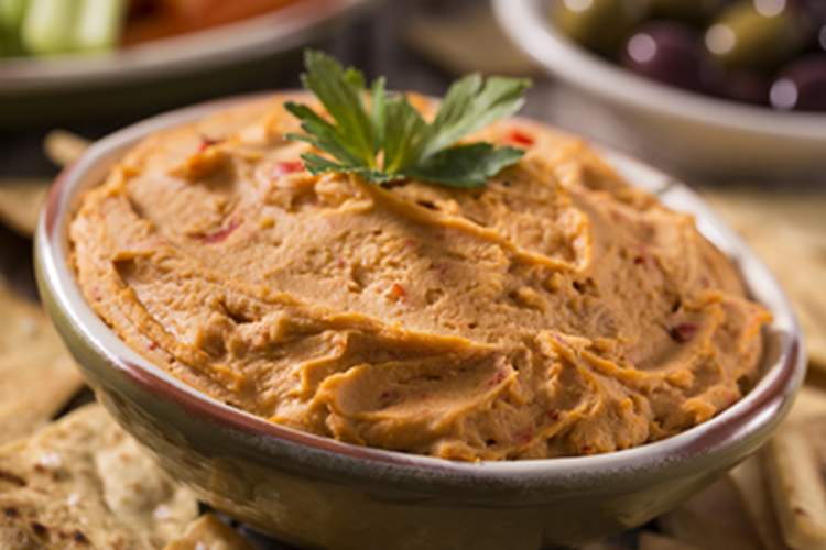 A bowl of roasted red pepper hummus.