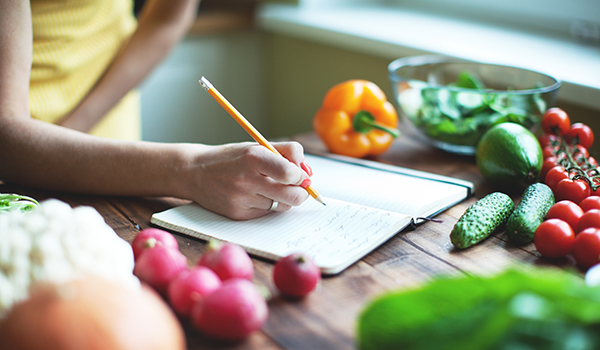 Woman writing in food notebook in kitchen