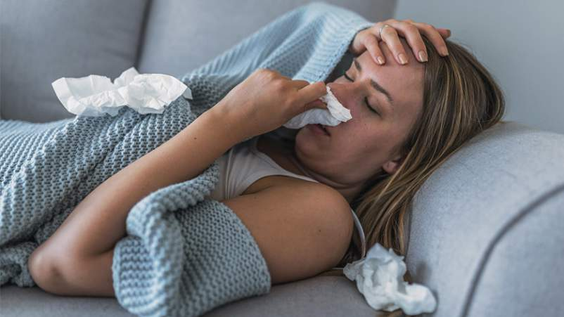 Woman with the flu on the couch at home.